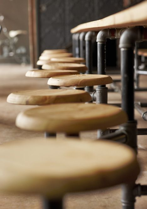 """Truth Coffee, Cape Town. """"Further café seating is provided by the vintage French worker chairs. The over scaled cog teeth on the edges of the Café tables tops, encourage groups of patrons to engage tables together to facilitate larger informal gatherings."""""""