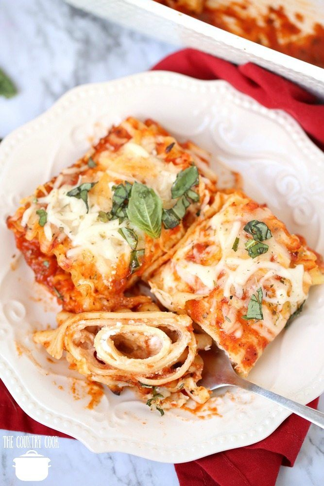Easy Meatless Lasagna Rolls on a white plate topped with fresh basil and a fork