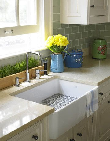 A Farmhouse Sink: The MHK110 Fireclay sink by Franke is 28 inches long and almost 8 inches deep — and seems even deeper since it has been undermounted. It's paired with Franke's MK28-36C stainless-steel grid, which allows dishes to drain. Smallbone makes the pewter knobs that open the cabinets. photo credit: Miki Duisterhof