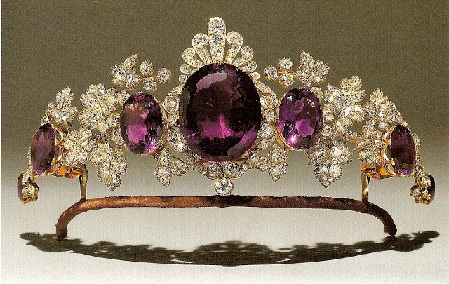 large Siberian amathyst mounted as a jewel with diamond-set honeysuckle motifs, c. 1810. At a later date it was made the centre of this amathyst and diamond tiara in the form of vine leaves that are a witty allusion to the purple stones. The word 'amathyst' derives from the Greek amethustos, literally meaning 'not drunken', referring to the belief that an amathyst placed in a glass of wine would allow one to drink without fear of intoxication. In the lore of the ancient lapidaries, the…