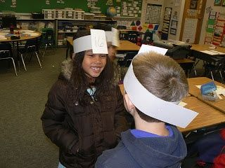 Students say your number has 1 tens and 4 ones. The person has to guess what number is on their head