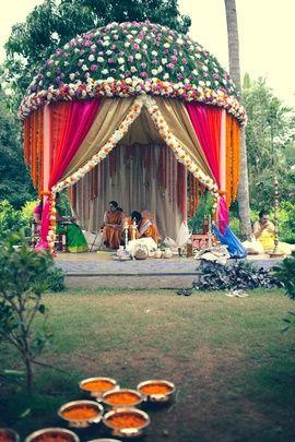 Wedding Decor - Floral Mandap Decor | WedMeGood Dome like Mandap Decor, Green pink and white mandap, with orange genda phool drops, hot pink and beige curtains with white and pink floral decor #wedmegood #decor #wedding #wmgdecor