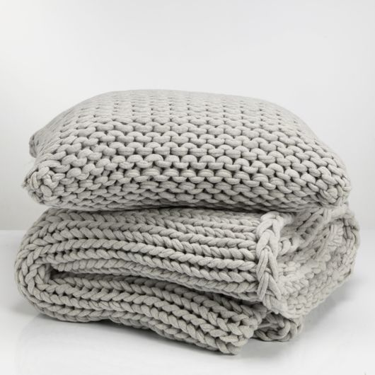 // Fede is an irresistibly soft blanket that fits nicely both as decoration and to have next to the skin. Made from knitted lambswool in light gray and hand-woven in a soft and airy designs for an exclusive feel. Braided edges for a beautiful finish. Combine with matching cushion covers.