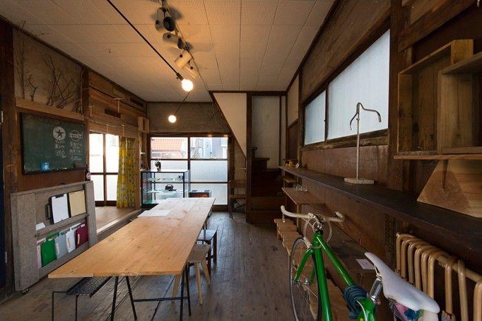 海山俊亮さんの家。1階のギャラリー。解体時に出た廃材を使って、劣化した壁をアレンジ。中央のテーブルは用途に応じて簡単にバラすことができる。