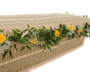 Pandanus natural woven coffin decorated with garland of flowers. Coffin from www.naturalendings.co.uk