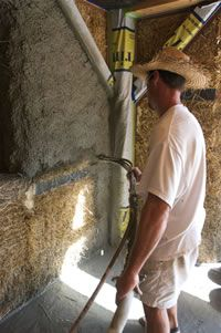 Earth Sweet Home - Off the Grid Straw Bale Construction - Spraying Plaster on the Bales