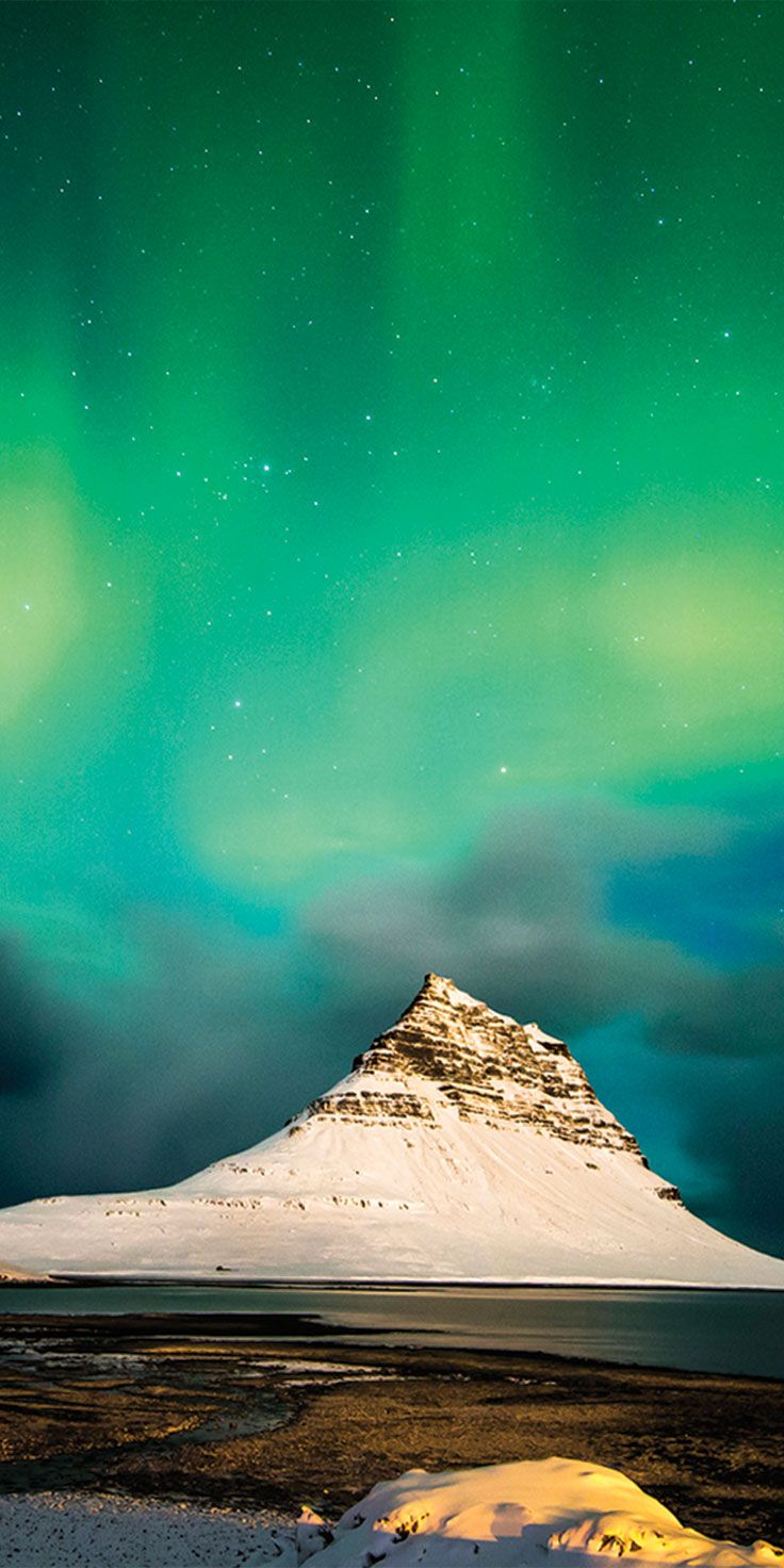 The Northern Lights illuminating the sky behind Kirkjufell Mountain in Iceland - by Sean Scott