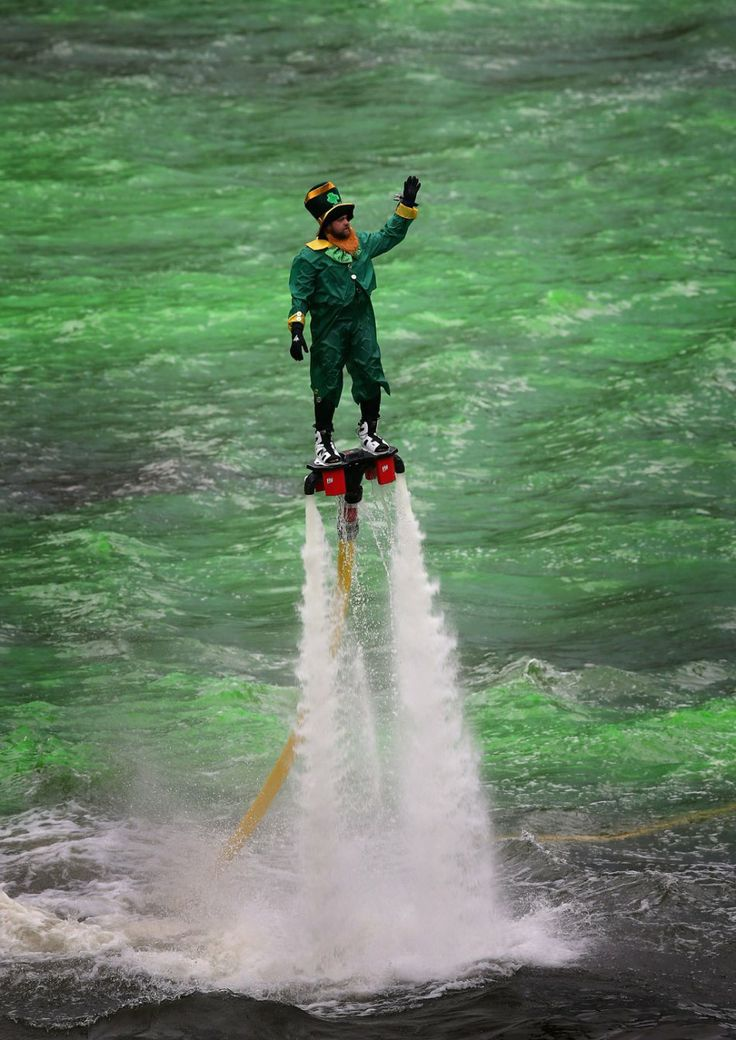 A man dressed as a leprechaun entertains the crowd on a water propelled Flyboard while workers dye the Chicago River green to kick off the c...