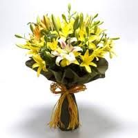 Yellow lilies with dark green paper packing, a bouquet for any special occasion.