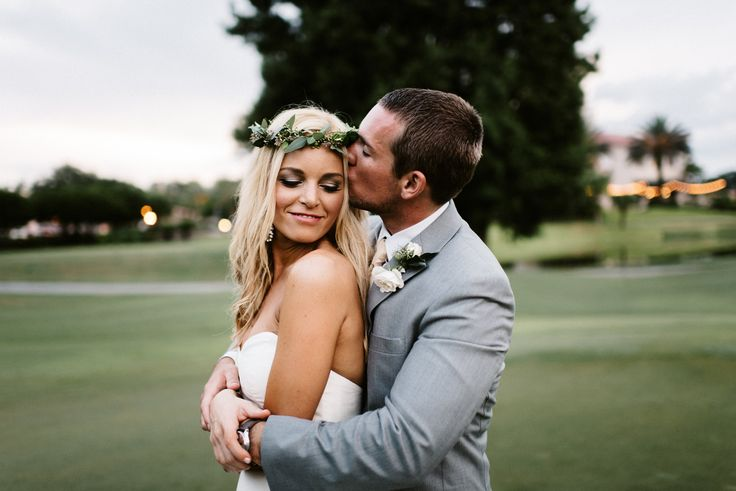 a kiss for his bride wearing a simple and organic flower crown of seeded eucalyptus.