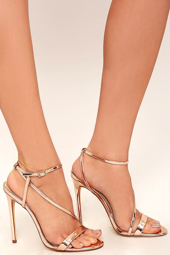 Set out in the Toulouse Rose Gold Dress Sandals and bask in the city lights! Metallic rose gold vegan leather forms a toe-strap, and matching asymmetrical strap that crosses the vamp, and wraps around the ankle. Gold buckle.