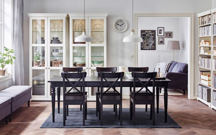 A large dining room with an extendable dining table and chairs in black and white glass-door cabinets.