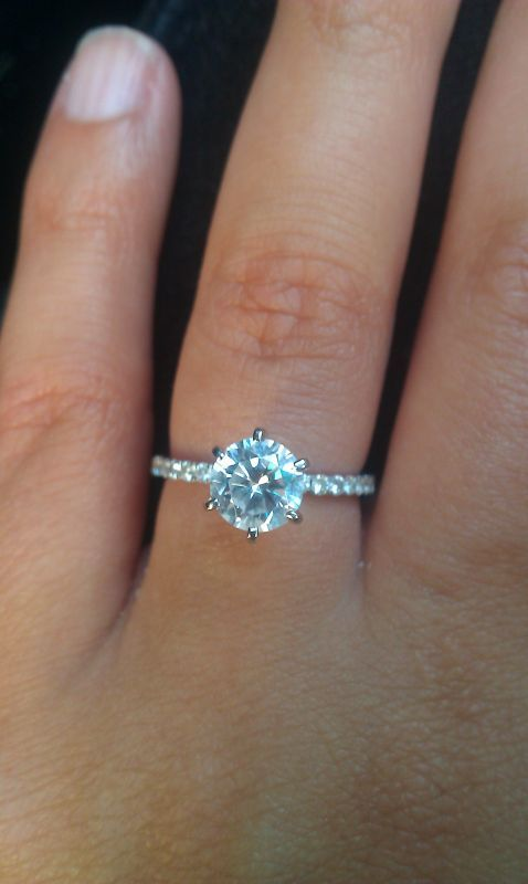 A round diamond ring with 6 prongs and a pave band