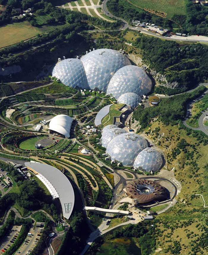 Eden Project s a visitor attraction in Cornwall in the United Kingdom, including the world's largest greenhouse. Inside the artificial biomes are plants that are collected from all around the world. The domes consist of hundreds of hexagonal and pentagonal, inflated, plastic cells supported by steel frames. The first dome emulates a tropical environment, and the second a Mediterranean environment. Invented by Jay Baldwin, architect Nicholas Grimshaw, opening 17.3.2001.