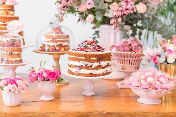 A ideia foi uma mesa de doces encantada, seguindo a tendência de diversos bolos pequenos ao invés de um único bolo. Naked cakes, arranjos de flores rústicos e travessas de doces em tons de cor de rosa.