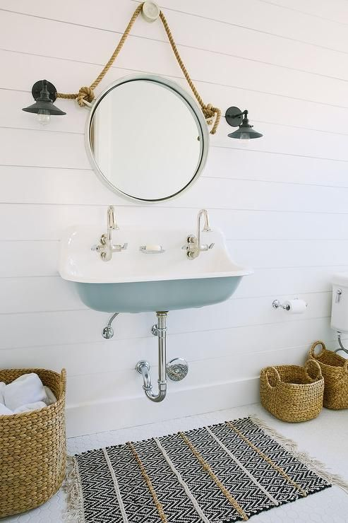 Cottage bathroom boasts a turquoise trough sink, Kohler Brockway Sink, fitted with two gooseneck faucets and a rope captain's mirror lining a shiplap wall illuminated by black vintage barn sconces alongside a black chevron bath mat.