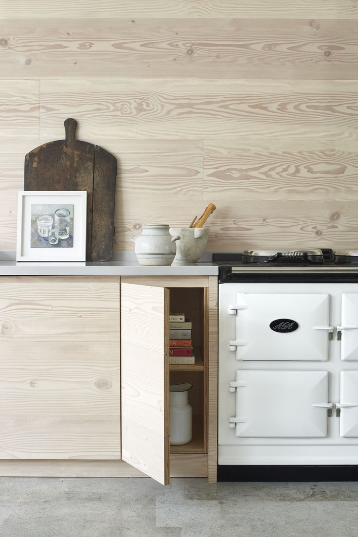 Dougls fir cabinets and wall paneling and a white Aga in a Scandinavian pale wood kitchen in London by Blakes London and House of Grey