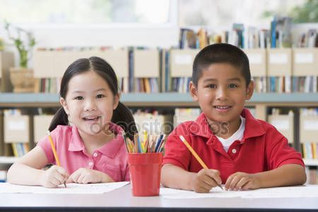 Download - Kindergarten children sitting at desk and writing in classroom — Stock Image #4759757