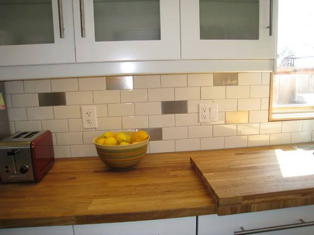 Stainless steel interspersed with white subway tile kitchen backsplash ...