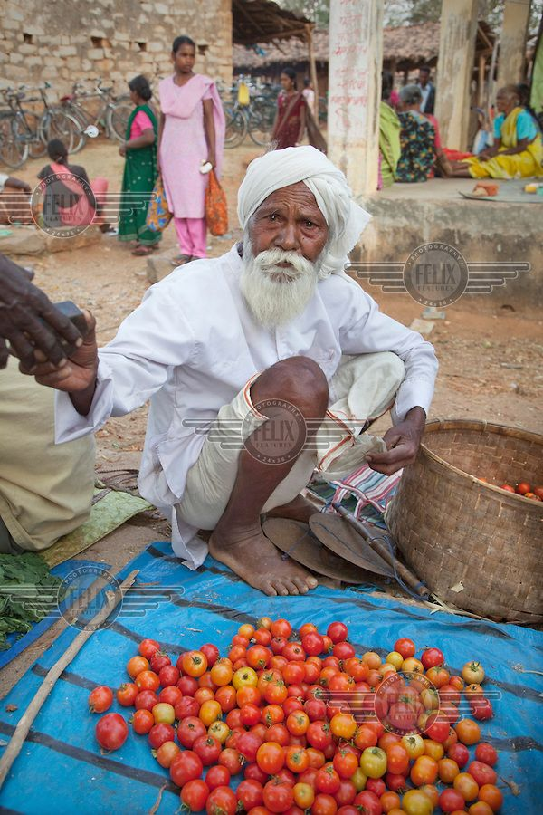 A man sells tomatoes at a market in the village of Tapkara in what is considered the Red Corridor of India; the base for Maoist guerrilla activities. During 2010 the Indian government began closing village markets such as this one in an attempt to deny Maoists support and supplies. However, this is having a severe impact on the economy of the affected villages and the farming community.