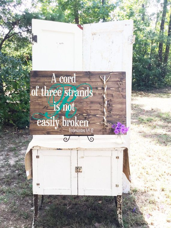 This beautiful wood sign features the scripture, A Cord of Three Strands is Not Easily Broken from Ecclesiastes 4: 9-12. It makes a wonderful alternative to a unity candle and we can customize the sign for your wedding with any of our 12 different vinyl lettering colors. Cords are included in the natural and white colors shown, we also include a smaller cord to tie the cords together after being braided. This board includes a hanger already attached on the back so it is ready to hang in…