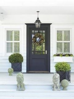White & Navy :: Dark Navy Front Door. With a yellow flowered wreath or yellow flowers in the planters.