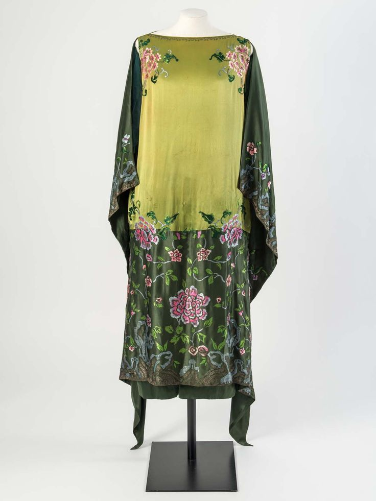 Green silk satin evening dress embroidered with floss silk and silver metal thread in a large floral and foliage design, about 1925.Worn by Molly Tondaiman, The Rani of Pudukkottai