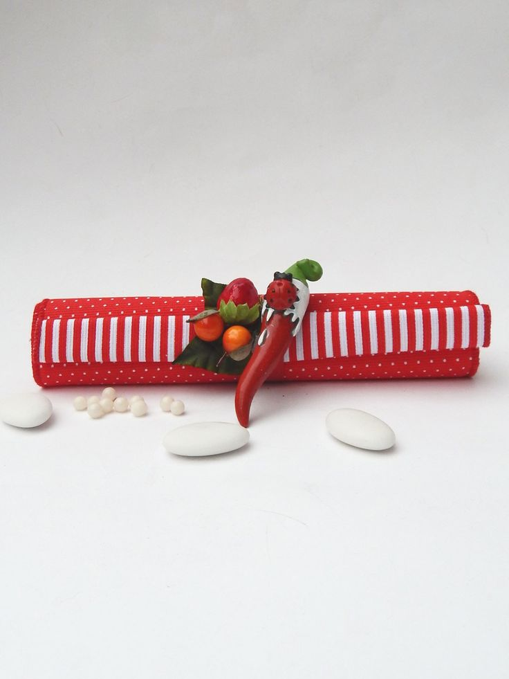 Corno rosso applicato su Sacchettino cilindrico rivestito in tessuto rifinito a mano, completo di Pergamena arrotolata e deliziose praline rosse ai cereali.