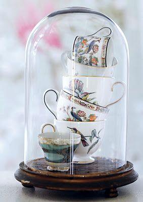 Bell jars with vintage tea sets for an Alice in Wonderland wedding theme