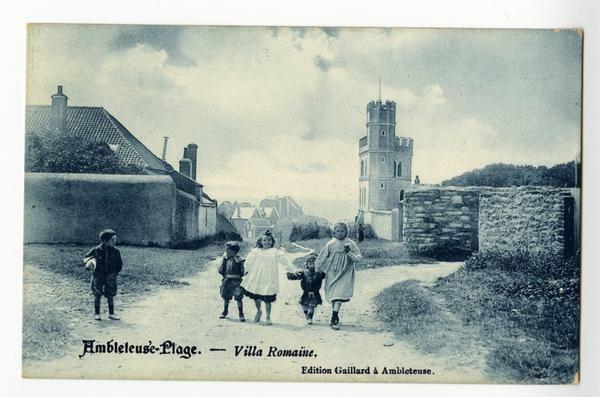 Agrandir l'image Carte postale en noir et blanc d'un chemin en terre battue, sur lequel avancent quatre enfants. Un cinquième, immobile sur le bas-côté, les regarde. Derrière eux, se dessinent les vestiges de la Villa romaine et l'entrée du bourg.