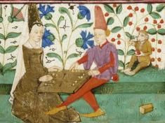 A medieval game of backgammon, with a monkey looking on.