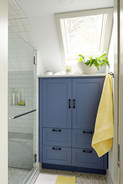 This Shaker-style bath cabinet stows towels and toiletries within arm's reach of the shower and makes use of available space under the sloped ceiling.