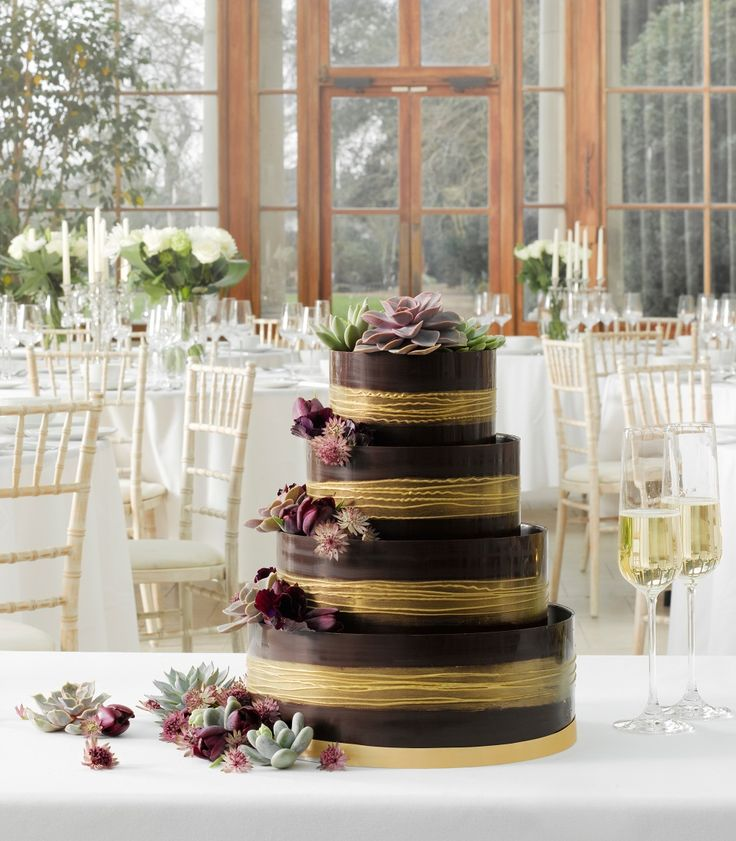 Four tier Chocoloate Marks & Spencer wedding cake decorated with gold banding and succulents