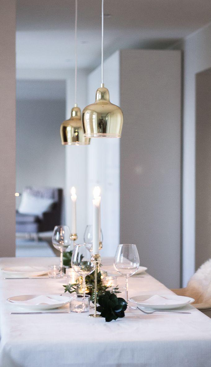 Winter and christmas table decor. Brass, white, green. Artek Golden Bell -lamps, Skultuna Tulip candlesticks, via Coffee Table Diary