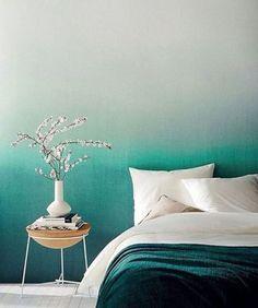 Na parede, a parte superior, verde clarinho, passa pelo verde água e fica mais escuro conforme se aproxima da cama. Ali, a manta completa a transição.