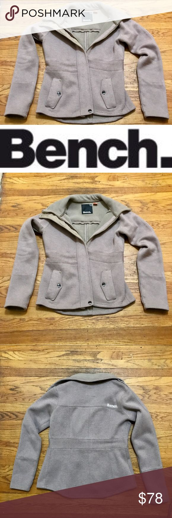 Wool Blend Fleece Lined Jacket from Bench Beautiful tan-ish/cement color wool knit, fleece lined winter jacket from Bench. Tagged as a large, but definitely a slim fitting large (please see measurements). This is a great jacket I loved and wore for a couple years but is in EUC, just picked up fresh from the dry cleaners ($15 saved for you!) This jacket has a funnel collar and thumb holes, plus the contrasting band around the waist is slimming! It is thin but warm. Does have a minor amount of…