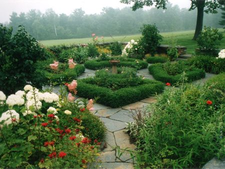 Another view of the Worthington, MA formal garden with manicured box hedges, carefully built stone wall, and ornamental birdbath.