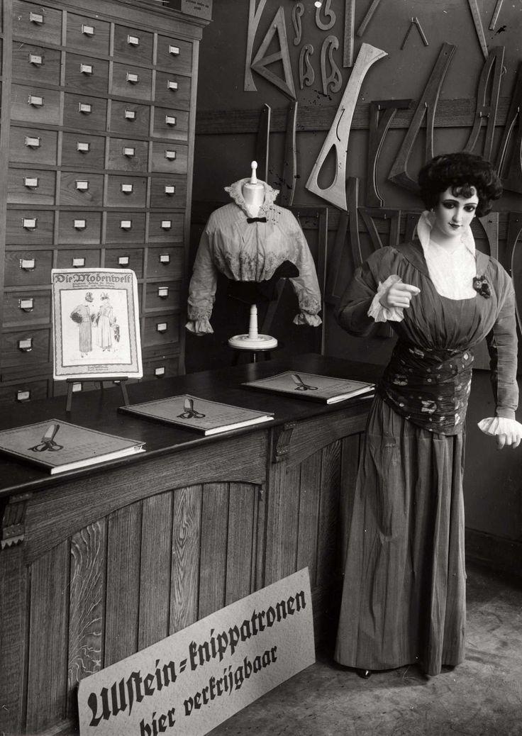 Naaien. Verkoopwinkel van knippatronen. Toonbank met allerlei voorbeeldboeken. Paspop en teken mallen. Nederland, Amsterdam, 1915.