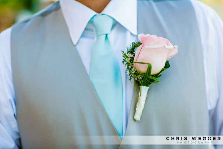 Tropical wedding suit for groom and groomsmen. Pink rose boutonniere, sea foam teal tie and grey wedding suit vest.