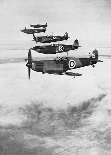 Six Supermarine Spitfire Mark Is of No. 19 Squadron, Royal Air Force, based at Duxford, Cambridgeshire (UK), flying in starboard echelon formation led by the Commanding Officer, Squadron Leader H.I. Cozens, in K9794.
