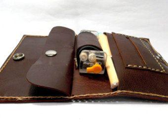 Funda de tabaco de liar, realizada en piel de ternera de primera calidad, cosida con hilo encerado, y con cierres a presión.  Con compartimentos para papel, filtros y tabaco.