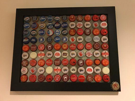Esta pieza es hecha a mano por Jaime Raglow de tapas de botellas de cervezas principalmente americanas. Las tapas se adhieren directamente al marco de cristal para que cree una sensación flotante. Cualquier color es la pared, va a ser el fondo de la bandera!  -Son principalmente rojo, blanco y azul. -Dimensiones: 11x 14 -Cap oro de la firma en la esquina  Este artículo fue creado con amor como una réplica de la primera obra de tapa de botella hecha Jaime. La primera bandera fue un regalo y…