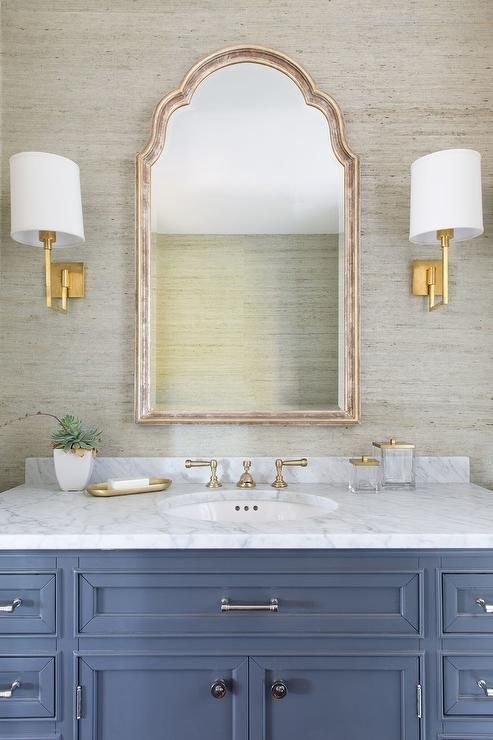 Aspect Library Sconces flank an arch mirror mounted to a wall covered in gray raffia wallpaper above a blue sink vanity accented with polished nickel hardware and a carrera marble countertop completed with an oval sink and satin nickel cross handle vintage faucet fixed in front of a carrera marble backsplash.