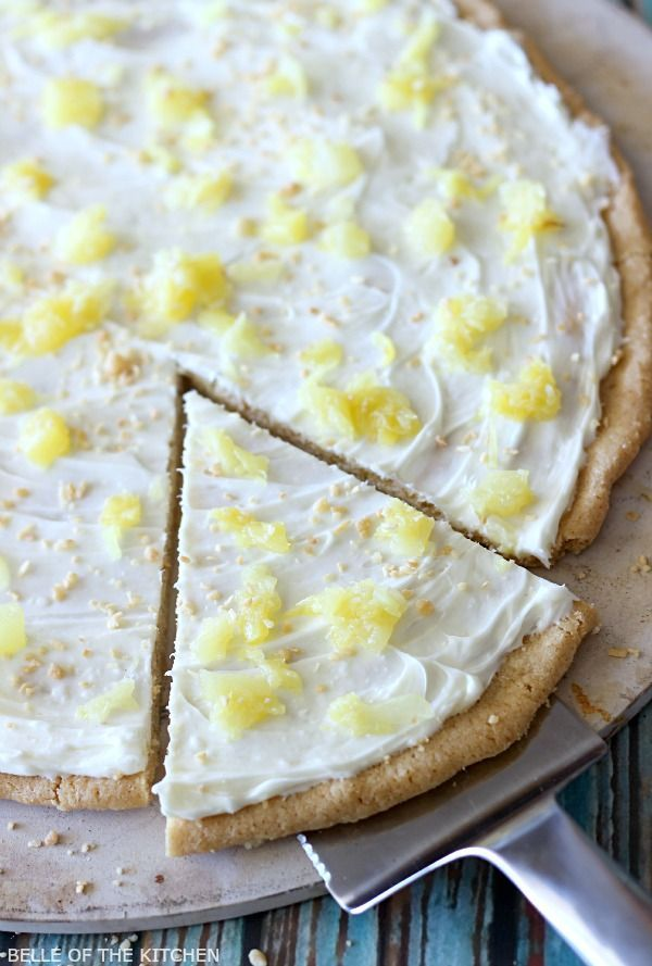 This Piña Colada Fruit Pizza is the perfect summer time treat! Made with a sugar cookie crust, a pineapple cream cheese frosting, and topped with juicy pineapple, you're going to want this all year round!