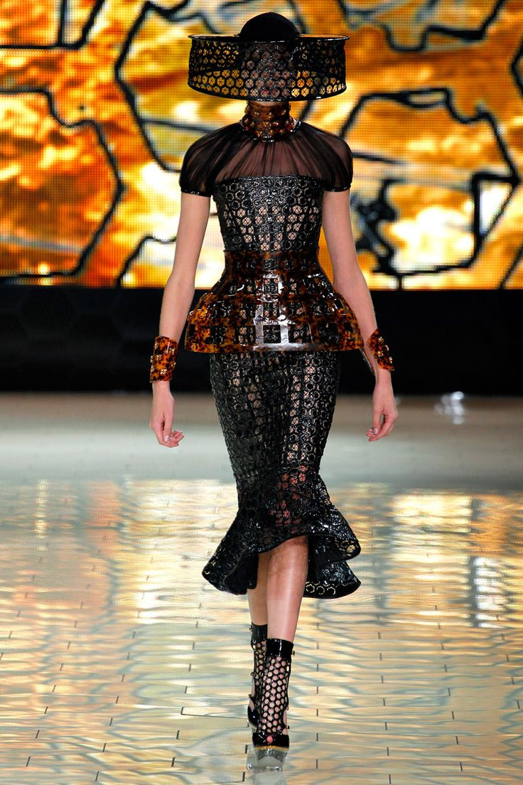 The laser cut honey comb pattern;  tortoiseshell-resin harness, collar, and cuffs; the bee keeper inspired hat, and the sheer shoulder--this look is so artistic!  Alexander McQueen Spring 2013