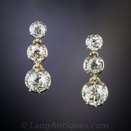 A graduated trio of bright white old mine-cut diamonds sparkle day and night from within articulated settings of silver over 14K gold in these over 5/8 inch long and lustrous ear drops dating from the beginning of the last century. Three are better than one! 2.30 carats total diamond weight.