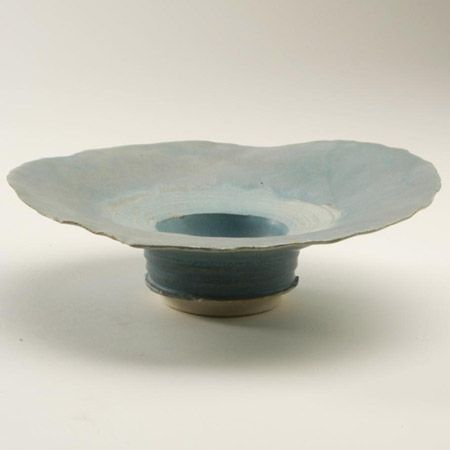 Mary White  Flanged dish in white porcelain body, fine blue glaze, oyster shell effect. Light blue around interior edge. Incised circular design emphasising centre    Gift of Welsh Arts Council, Cardiff Symposium August 1975  20cm wide  Mark: Painted monogram on foot  c926