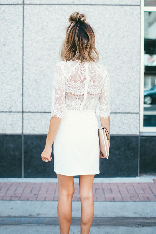 Little white dress with lace bodice and white skirt, blush clutch, and half top knot