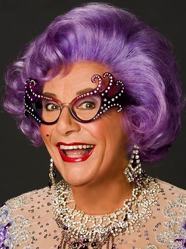 """Dame Edna is a character created and played by Australian dadaist performer and comedian, Barry Humphries, famous for her lilac-coloured or """"wisteria hue"""" hair and cat eye glasses or """"face furniture,"""" ..."""