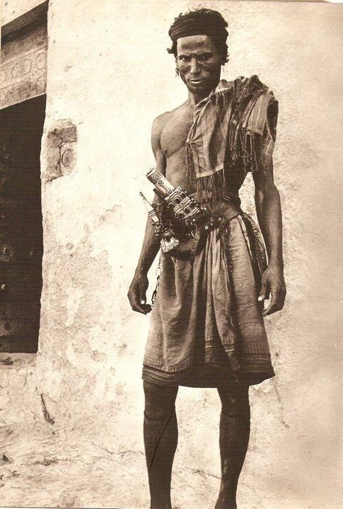 A man from Jazan, a port city in Southwest Saudi Arabia on the edge of Yemen, which explains that decorative blade at his waist. He looks like a Navajo brave. Uncredited, undated.